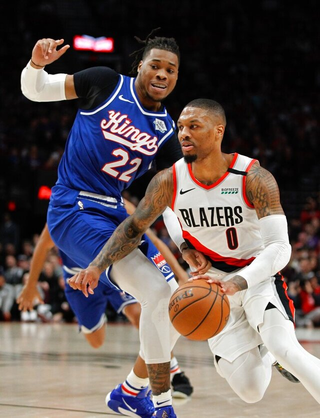 Portland Trail Blazers guard Damian Lillard, right, drives past Sacramento Kings center Richaun Holmes during the first half of an NBA basketball game in Portland, Ore., Saturday, March 7, 2020. (AP Photo/Steve Dipaola)