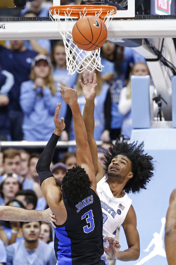 North Carolina's Coby White defends as Duke's Tre Jones (3) drives to the basket during the first half of an NCAA college basketball game in Chapel Hill, N.C., Saturday, March 9, 2019. (AP Photo/Gerry Broome)
