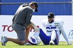 A trainer examines Buffalo Bills running back Taiwan Jones after he took a spill during an NFL football training camp in Orchard Park, N.Y., Sunday, Aug. 23, 2020. (James P. McCoy/The Buffalo News via AP, Pool)