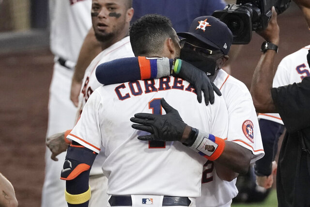 CORRECTS TO THURSDAY, OCT. 15, 2020, NOT TUESDAY, DEC. 15, 2020 - Houston Astros Carlos Correa is hugged by Houston Astros manager Dusty Baker Jr. after his walk off home run during the ninth inning in Game 5 of a baseball American League Championship Series, Tuesday, Dec. 15, 2020, in San Diego. The Astros defeated the Rays 4-3 and the Rays lead the series 3-2 games. (AP Photo/Ashley Landis)