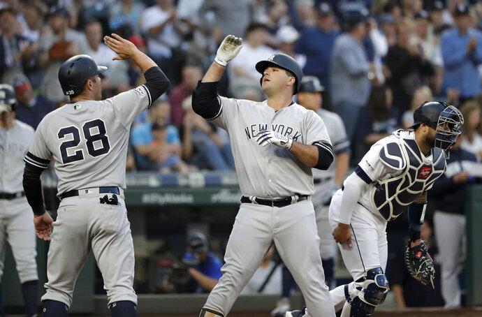 New York Yankees' Austin Romine (28) congratulates Mike Ford on Ford's two-run home run as Seattle Mariners catcher Omar Narvaez heads to the mound in the second inning of a baseball game Monday, Aug. 26, 2019, in Seattle. (AP Photo/Elaine Thompson)