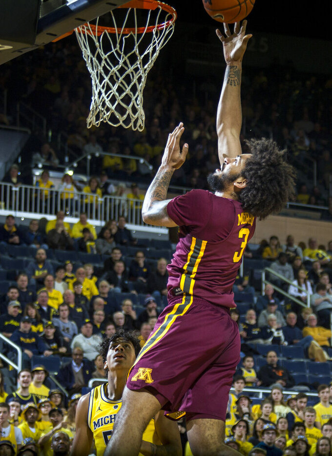 Minnesota forward Jordan Murphy (3) makes a basket, watched by Michigan guard Zavier Simpson, bottom, in the first half of an NCAA college basketball game at Crisler Center in Ann Arbor, Mich., Tuesday, Jan. 22, 2019. (AP Photo/Tony Ding)