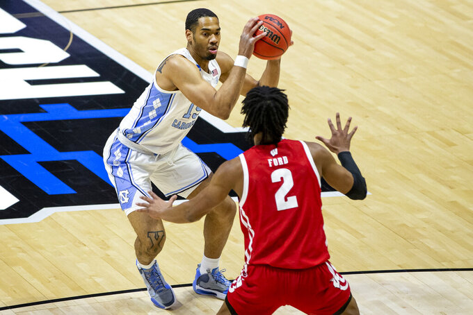 North Carolina's Garrison Brooks, left, drives in against Wisconsin's Aleem Ford (2) during the first half of a first-round game in the NCAA men's college basketball tournament, Friday, March 19, 2021, at Mackey Arena in West Lafayette, Ind. (AP Photo/Robert Franklin)