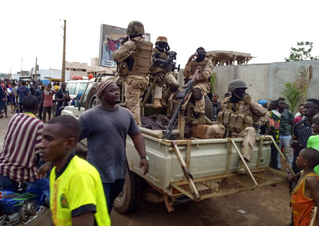 Malian troops and citizens gather outside the private residence of Mali's President Ibrahim Boubacar Keita in Bamako, Mali Tuesday, Aug. 18, 2020. Mutinous soldiers surrounded the private residence of Keita on Tuesday, firing shots into the air and a West African regional official confirmed that the president and prime minister had been detained, following several months of demonstrations calling for his resignation. (AP Photo)