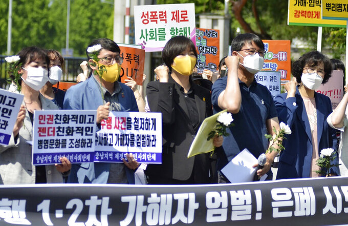 """Members of the Justice Party and civic groups attend at a press conference calling for the punishment of air force officials involved in any cover-up, in front of the main gate of air force base in Seosan, South Korea, Friday, June 4, 2021. South Korea's air force chief stepped down Friday in the face of public anger over the death of a female master sergeant whose family says she killed herself after being sexually abused by a male colleague.  A part of letters read """"Punishment! and Cover-up.""""(Lee Eun-pa/Yonhap via AP)"""