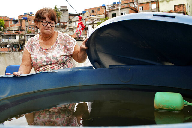 Laura Maria de Almeida shows her home's water storage container, full of cloudy, smelly water, on her roof in the Complexo de Alemao slum of Rio de Janeiro, Brazil, Thursday, Jan.16, 2020. De Almeida said cloudy water isn't unusual in her community, but police are investigating workers at a state utility after smelly tap water flowed into dozens of neighborhoods of the Brazilian city. (AP Photo/Ricardo Borges)