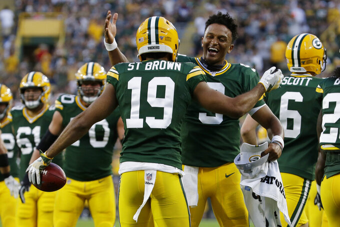 Green Bay Packers wide receiver Equanimeous St. Brown (19) celebrates recovering a muffed punt for a touchdown, with quarterback DeShone Kizer (9) during the first half of an NFL preseason football game against the Houston Texans on Thursday, Aug. 8, 2019, in Green Bay, Wis. (AP Photo/Mike Roemer)