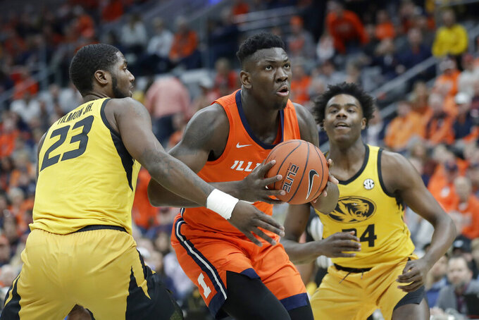 FILE - In this Dec. 21, 2019, file photo, Illinois' Kofi Cockburn, center, heads to the basket past Missouri's Jeremiah Tilmon and Kobe Brown during the first half of an NCAA college basketball game in St. Louis. The return of stars Ayo Dosunmu and Cockburn has brought a sense of optimism and high expectations to an Illinois program that saw a magical season abruptly halted by the pandemic in March. (AP Photo/Jeff Roberson, File)