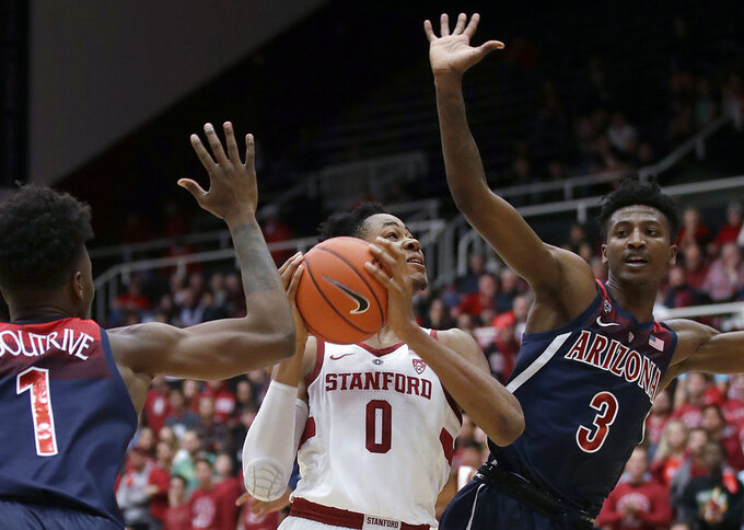 Stanford forward KZ Okpala (0) shoots between Arizona guards Devonaire Doutrive (1) and Dylan Smith (3) during the first half of an NCAA college basketball game in Stanford, Calif., Wednesday, Jan. 9, 2019. (AP Photo/Jeff Chiu)