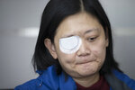 In this Wednesday, Dec. 4, 2019, photo, Veby Mega Indah, an injured Indonesian video journalist, bites her lips during an interview with The Associated Press in the Wan Chai area of Hong Kong. More than two months after being blinded in one eye by what she believes was a projectile fired by riot police, Indah is still seeking answers. On Sept. 29, 2019, Indah was among a group of reporters covering one of the hundreds of clashes between armed police and anti-government protesters that have broken out almost daily over the past six months. (AP Photo/Vincent Thian)