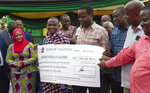 In this image made from video taken Wednesday, June 24, 2020, miner Saniniu Laizer, center-left, receives a cheque from government officials for 7,744,152,703.82 Tanzanian Shillings ($3.4 million), at a ceremony in Mererani, Tanzania Wednesday, June 24, 2020. The small-scale miner has become an overnight millionaire after unearthing two of the biggest rough tanzanite gemstones ever found, weighing 20 pounds (9 kg) and 11 pounds (5 kg), which the government bought for preservation for $3.4 million. (AP Photo)