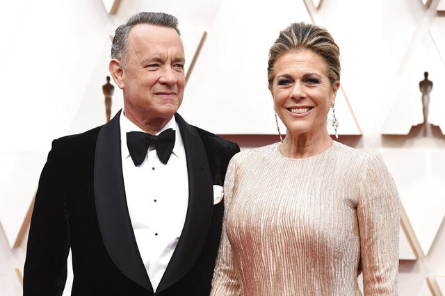 "FILE - In this Sunday, Feb. 9, 2020 file photo, Tom Hanks, left, and Rita Wilson arrive at the Oscars at the Dolby Theatre in Los Angeles. On Friday, March 13, 2020, The Associated Press reported on a manipulated image circulating online depicting actor Tom Hanks quarantined at a hospital in Australia with a volleyball that looks like Wilson, his make-believe friend in the movie ""Cast Away."" It first circulated as satire. Hanks is in Australia shooting an Elvis Presley biopic directed by Baz Luhrmann. Hanks shared the news about his positive tests on Twitter Wednesday. (Photo by Jordan Strauss/Invision/AP)"