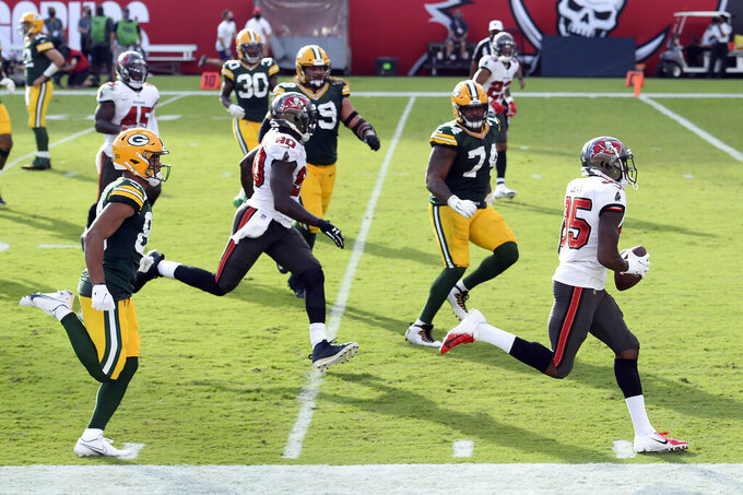 Tampa Bay Buccaneers cornerback Jamel Dean (35, right) heads for the endzone after intercepting a pass by Green Bay Packers quarterback Aaron Rodgers and returning it for a score during the first half of an NFL football game Sunday, Oct. 18, 2020, in Tampa, Fla. (AP Photo/Jason Behnken)