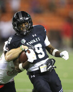 UNLV defensive back Dalton Baker (33) can't stop Hawaii wide receiver JoJo Ward (19) from making a touchdown to tie the game during the fourth quarter of an NCAA college football game, Saturday, Nov. 17, 2018, in Honolulu. Hawaii would go on to defeat UNLV 35-28. (AP Photo/Marco Garcia)