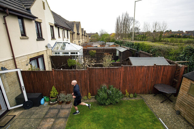 James Campbell runs a charity marathon to raise funds for the NHS, in his garden, while the country is in lockdown to control the spread of coronavirus, in Cheltenham, England, Wednesday April 1, 2020. The former international athlete is spending his birthday running - in his seven-metre-long back garden - and will take over 7,000 shuttles back and forth to finish the 26.2-mile marathon. (Jacob King/PA via AP)