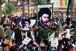Followers of Shiite cleric Muqtada al-Sadr, in the posters, gather in Tahrir Square, Baghdad, Iraq, Friday, Nov. 27, 2020. Thousands took to the streets in Baghdad on Friday in a show of support for a radical Iraqi cleric ahead of elections slated for next year, stirring fears of a spike in coronavirus cases. (AP Photo/Khalid Mohammed)