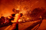 Firefighters battling the Bond Fire haul a hose while working to save a home in the Silverado community in Orange County, Calif., on Thursday, Dec. 3, 2020. (AP Photo/Noah Berger)