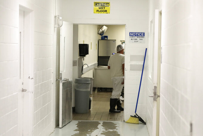 In this photo taken Sept. 10, 2019, a detainee works in a kitchen area at the GEO Group's immigration jail in Tacoma, Wash., during a media tour. After nearly four years of litigation and pandemic-related delays, a federal jury on Tuesday, June 15, 2021, began deliberating whether the GEO Group must pay minimum wage to detainees who perform cooking, cleaning and other tasks at the facility – instead of the $1 per day they typically receive. (AP Photo/Ted S. Warren)