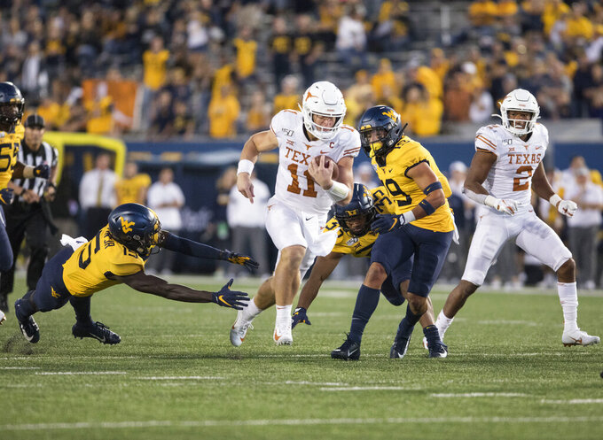 Texas quarterback Sam Ehlinger (11) evades West Virginia safety Kerry Martin Jr. (15) on his way to score a touchdown during the second half of an NCAA college football game Saturday, Oct. 5, 2019, in Morgantown, W.Va. (AP Photo/Raymond Thompson)