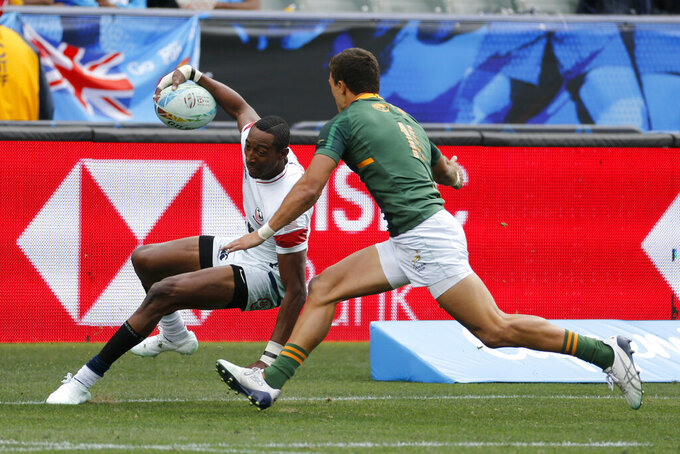 FILE - In this March 1, 2020, file photo, United States' Perry Baker, left, runs away from South Africa's Muller Du Plessis during the Los Angels Sevens rugby tournament in Carson, Calif. This is one sport where COVID-19 restrictions cannot separate 14 humans competing for a ball in 14-minute chunks of time, a dozen times a day. (AP Photo/Ringo H.W. Chiu, File)