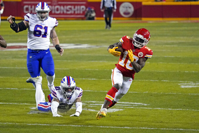 Kansas City Chiefs wide receiver Tyreek Hill (10) runs from Buffalo Bills safety Jordan Poyer (21) and defensive tackle Justin Zimmer (61) after catching a pass during the second half of the AFC championship NFL football game, Sunday, Jan. 24, 2021, in Kansas City, Mo. (AP Photo/Jeff Roberson)