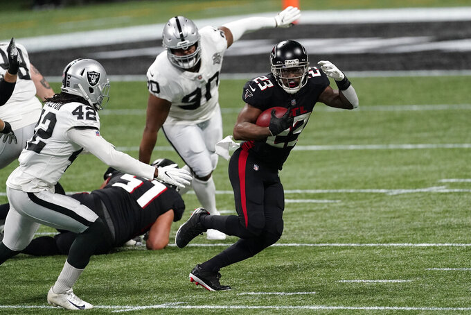 Atlanta Falcons running back Brian Hill (23) runs against Las Vegas Raiders outside linebacker Cory Littleton (42) during the first half of an NFL football game, Sunday, Nov. 29, 2020, in Atlanta. (AP Photo/John Bazemore)