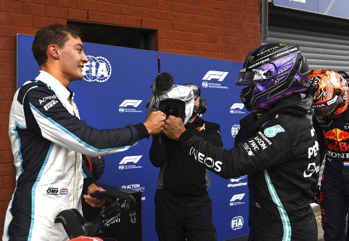 Second place Williams driver George Russell of Britain, left, fist bumps with third place Mercedes driver Lewis Hamilton of Britain after the qualification ahead of the Formula One Grand Prix at the Spa-Francorchamps racetrack in Spa, Belgium, Saturday, Aug. 28, 2021. The Belgian Formula One Grand Prix will take place on Sunday. (John Thys, Pool Photo via AP)