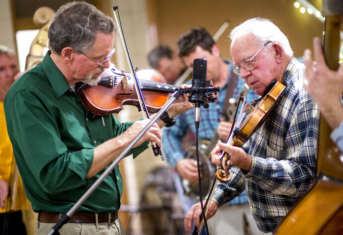In this Feb. 26, 2016, photo, Walter Grooms, of Harrisonburg, Va. at left, plays the fiddle with Ira Carte, of Mount Jackson, Va., during a Friday night bluegrass jam session at the New Market Community Center in New Market, Va. Since the March 2020 COVID-19 pandemic, musicians have adapted to streaming shows online and collaborating with distant artists for songs in solidarity, but revenue and environmental changes have caused some music makers to reflect on and experiment with their artistic intentions. (Daniel Lin/Daily News-Record via AP)