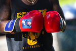 In this Tuesday, May 26, 2020 photo, Damiene Palmer, of Fineview and an amateur boxer, uses boxing gloves with the image of his son Damiene Jr. while practicing boxing techniques with Gerald Sherrell, of Bellevue and pro fighter and season 5 Contender finalist, outside of Sherrell's home  in Bellevue, Pa.Since the closing of gym's due to the COVID-19 pandemic, boxers and MMA fighters have taken to the streets and using makeshift home gym's to stay in shape while quarantining. (Michael M. Santiago/Pittsburgh Post-Gazette via AP)