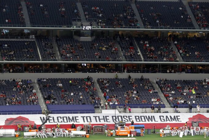 "A banner along the sideline at AT&T Stadium reads, ""Welcome To The Rose Bowl Game"", as fans watch the teams warm up before the Rose Bowl NCAA college football game between Notre Dame and Alabama in Arlington, Texas, Friday, Jan. 1, 2021. (AP Photo/Roger Steinman)"