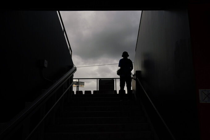 An Olympic worker is silhouetted against clouds at the Fukushima Azuma Baseball Stadium ahead of a baseball game between Japan and the Dominican Republic at the 2020 Summer Olympics, Tuesday, July 27, 2021, in Fukushima, Japan. (AP Photo/Jae C. Hong)