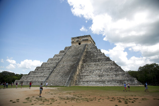 "FILE - In this Aug. 3, 2018 file photo, tourists walk at the Mayan ruins of Chichen Itza in Mexico's Yucatan Peninsula. Experts in Mexico said Wednesday, Oct. 14, 2020, that they have detected more than 2,000 pre-Hispanic ruins or clusters of artefacts along the proposed route of the president's controversial ""Maya Train"" project on the Yucatan peninsula, which could slow down the already disputed project. (AP Photo/Eduardo Verdugo)"