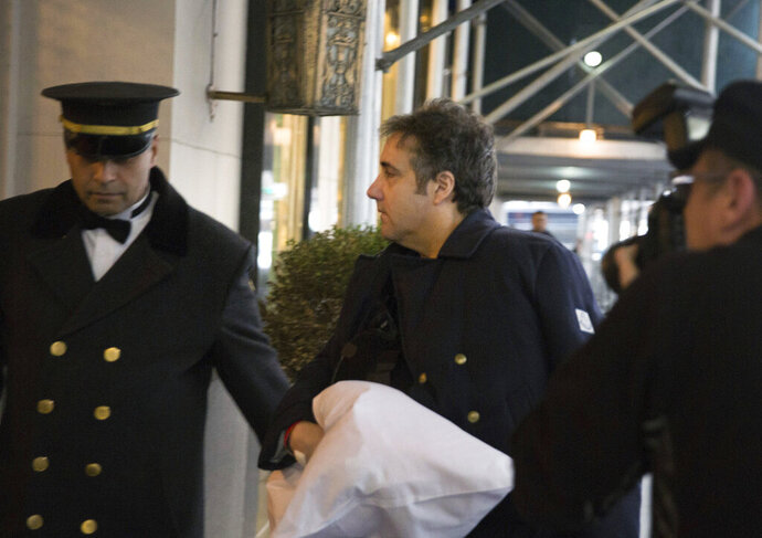 """FILE - In this Jan. 18, 2019, file photo, Michael Cohen arrives at his home in New York with his left arm in a sling supported by a pillow. An attorney for  Cohen says his closed-door testimony before the Senate intelligence committee has been postponed """"due to post-surgery medical needs."""" President Donald Trump's former personal lawyer is under subpoena from the committee and was scheduled to talk to the panel Tuesday. (AP Photo/Kevin Hagen)"""