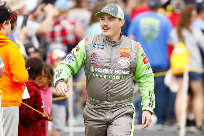 Brett Moffitt walks to his car after driver introductions before a NASCAR Truck Series auto race, Sunday, June 16, 2019, at Iowa Speedway in Newton, Iowa. Moffitt was declared the winner of the race after apparent winner Ross Chastain's car failed a post-race inspection. (AP Photo/Charlie Neibergall)