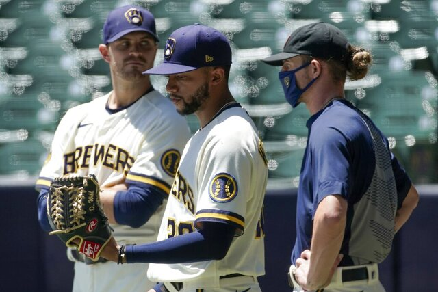 Milwaukee Brewers' Justin Grimm, Devin Williams and Josh Hader watch during a practice session Monday, July 13, 2020, at Miller Park in Milwaukee. (AP Photo/Morry Gash)