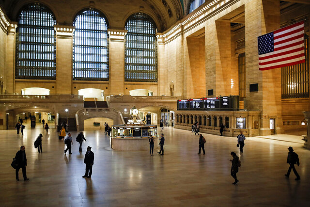A MTA conductor stands in a light beam at Grand Center Terminal that is sparsely populated during rush hour due to COVID-19 concerns, Friday, March 20, 2020, in New York. New York Gov. Andrew Cuomo is ordering all workers in non-essential businesses to stay home and banning gatherings statewide.