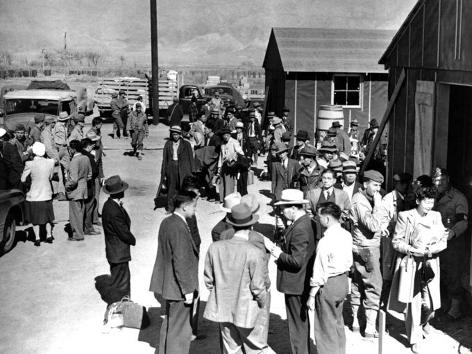 FILE - This March 23, 1942 photo shows the first arrivals at the Japanese evacuee community established in Owens Valley in Manzanar, Calif. Roughly 120,000 Japanese immigrants and Japanese-Americans were sent to camps that dotted the West because the government claimed they might plot against the U.S. The location is featured in a collection of mini-essays by American writers published online by the Frommer's guidebook company about places they believe helped shape and define America.  (AP Photo/File)