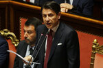 FILE - In this Tuesday, Aug. 20, 2019 file photo, Italian Premier Giuseppe Conte, right, is flanked by Deputy-Premier Matteo Salvini as he addresses the Senate in Rome. Italy's populist 5-Star Movement has asked, Wednesday, Aug. 28, 2019, the nation's president to give caretaker Premier Giuseppe Conte the mandate to form a new coalition government, a week after the one he led for 14 months collapsed. (AP Photo/Gregorio Borgia, File)