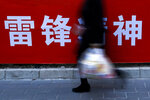 A woman carries her groceries past a Chinese propaganda board depicting
