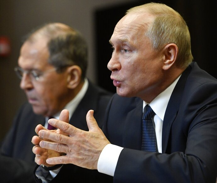Russian President Vladimir Putin, right, gestures while speaking to Chinese Foreign Minister Wang Yi during their meeting in the Bocharov Ruchei residence in the Black Sea resort of Sochi, Russia, Monday, May 13, 2019. Russian Foreign Minister Sergey Lavrov is at left. (Alexander Nemenov/Pool Photo via AP)