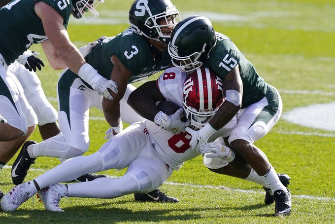 Indiana running back Stevie Scott III (8) is stopped by Michigan State cornerback Angelo Grose (15) during the first half of an NCAA college football game, Saturday, Nov. 14, 2020, in East Lansing, Mich. (AP Photo/Carlos Osorio)
