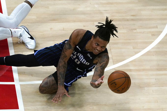 Orlando Magic guard Markelle Fultz (20) passes as he falls to the court during the second half of an NBA basketball game against the Atlanta Hawks, Sunday, Dec. 13, 2020, in Atlanta. (AP Photo/John Bazemore)