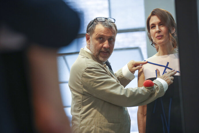 In this Sept. 4, 2019, photo, designer Herve Pierre fits Emmy-nominated actress Jessica Hecht with a dress for her to wear at the Creative Arts Emmy Awards, at Atelier Caito for Herve Pierre in New York. (AP Photo/Mary Altaffer)