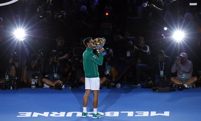 Serbia's Novak Djokovic kisses the Norman Brookes Challenge Cup after defeating Austria's Dominic Thiem in the final of the Australian Open tennis championship in Melbourne, Australia, early Monday, Feb. 3, 2020. (AP Photo/Dita Alangkara)