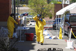 In this May 7, 2020, photo, medical staff from Rehoboth McKinley Christian Hospital put on protective equipment as they work at a drive-thru coronavirus testing site outside the hospital in Gallup, N.M. Of about 500 medical and support staff, at least 32 hospital workers have become infected, and doctors and nurses say that they all live with the fear of spreading the virus to their colleagues and relatives. (AP Photo/Morgan Lee)
