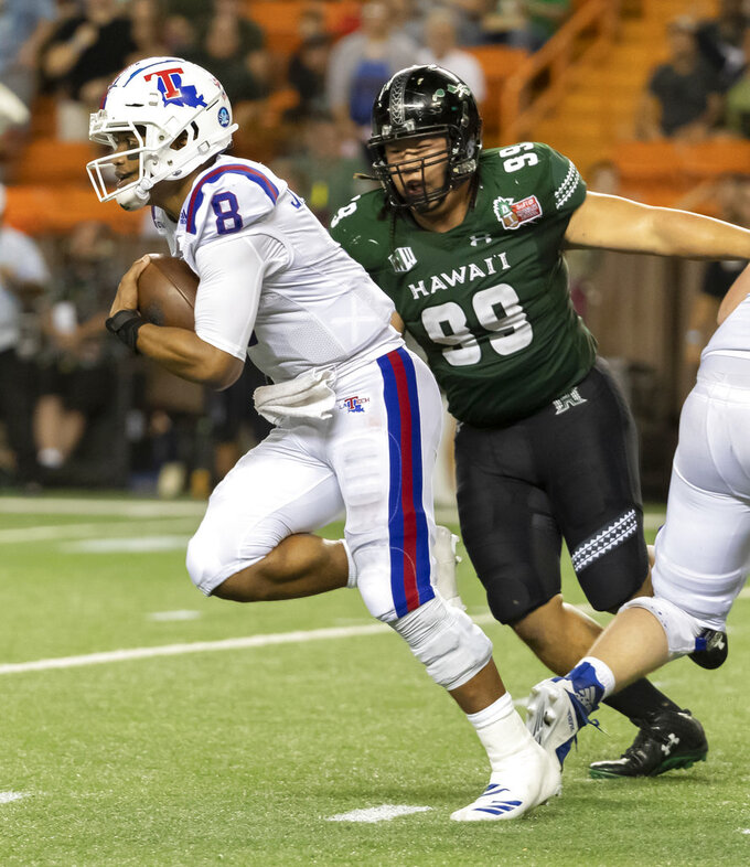 Louisiana Tech quarterback J'Mar Smith (8) scrambles out of the pocket while being chased by Hawaii defensive lineman Zeno Choi (99) in the second half of the Hawaii Bowl NCAA college football game, Saturday, Dec. 22, 2018, in Honolulu. (AP Photo/Eugene Tanner)