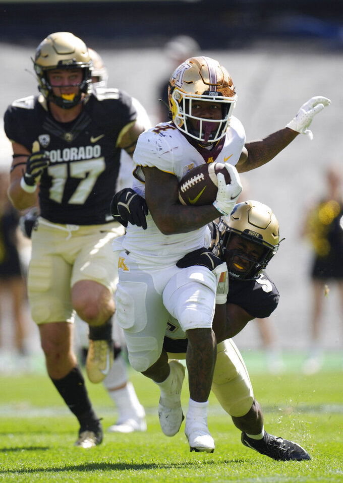 Minnesota running back Mar'Keise Irving, front, is dragged down by Colorado safety Mark Perry as defensive end Blayne Toll trails the play in the second half of an NCAA college football game Saturday, Sept. 18, 2021, in Boulder, Colo. Minnesota won 30-0. (AP Photo/David Zalubowski)