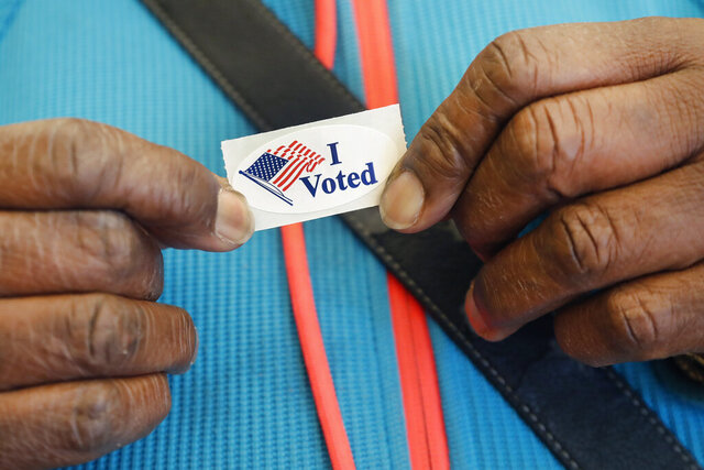 Loretta Haynes, of Cambridge, Mass., shows her sticker, Monday, Feb. 24, 2020, at the Cambridge City Hall annex, after she voted on the first morning of early voting in Massachusetts. (AP Photo/Elise Amendola)