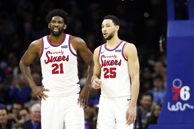 FILE - In this Dec. 13, 2019, file photo, Philadelphia 76ers' Ben Simmons, right, and Joel Embiid talk during an NBA basketball game against the New Orleans Pelicans in Philadelphia. The 76ers new coach Doc Rivers is set to begin his first training camp with the team trying to unlock the potential of All-Stars Ben Simmons and Joel Embiid.(AP Photo/Matt Slocum, File)