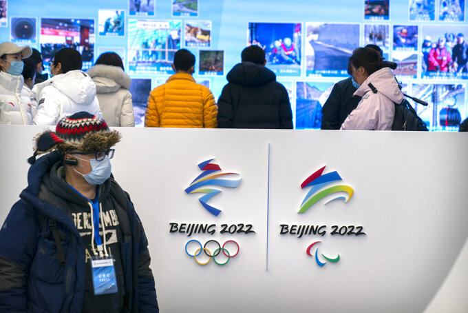 A journalist wearing a face mask to protect against the spread of the coronavirus looks at an exhibit at a visitors center at the Winter Olympic venues in Yanqing on the outskirts of Beijing, Friday, Feb. 5, 2021. Beijing Olympic organizers showed off the downhill skiing venue and the world's longest bobsled and luge track Friday, one year ahead of the scheduled opening of the 2022 Olympic Winter Games. (AP Photo/Mark Schiefelbein)